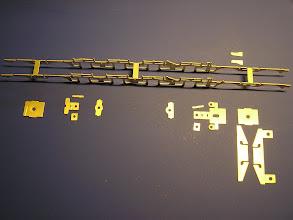 """Photo: Rám pojezdu - všechny """"nosné"""" součásti z mosazi 0.5 mm (zleva): - příčník nad předním běžným podvozkem - konzole pro uchycení ojnice předního podvozku - příčník pro uchycení sbírání proudu - přední - příčník pro uchycení sbírání proudu - zadní - kombinovaný příčník (ojnice zadního podvozku, motor, brzdové válce) - příčník nad zadním podvozkem - nosníky tendru"""
