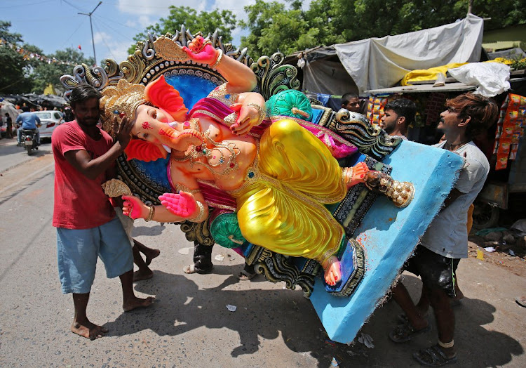 Artisans carry an idol of Hindu god Ganesh, the deity of prosperity, to load it onto a truck heading to a place of worship in India.