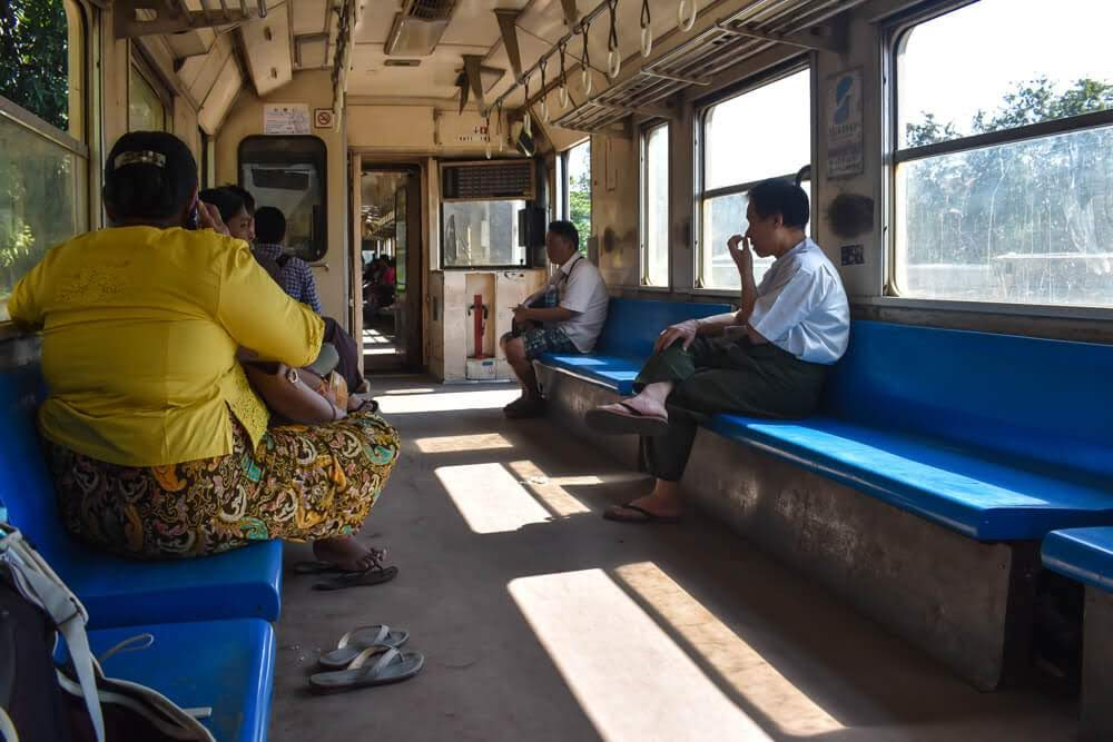 women in longyi sitting on circle line yangon burma.jpg