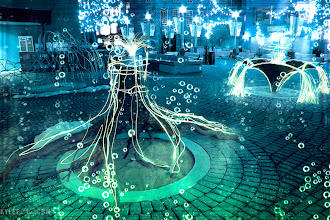 Photo: From the blog http://www.kylefoto.com  Some of the first long exposures I've ever taken! I did this while in photography school in 2005.   *Photographic Details:* Sneaking into a courtyard with these interesting sculptures I tried out the light drawing aspect of light painting. Here I would use an LED light to physically trace the outline of these objects, manually painting every stroke of light that you see on the tree trunk and sparkling structure in the background. I wanted to make it look surreal, as if the structure in the background was overflowing with energy. This is actually multiple 30 second exposures mashed together to combine into one ultra long exposure, with a minimum of image noise. Because I was wearing dark clothes and moving a lot, my body becomes invisible in the long exposure and only the light from the flashlight shows up! Other things like the colour and bubbles were added in photoshop.