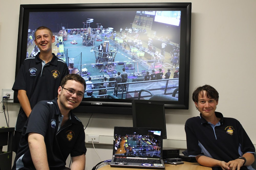 Kaputar Klockworks team members Nick Tomlinson, Will Lonergan and Tyrone Hensley show off some of the action on the big screen from the FIRST Robotics championship at Sydney Olympic Park.