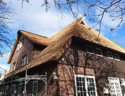 Proces kładzenia strzechy na budynku