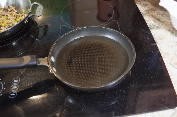 Place about 1 inch (2.5cm) of oil in a shallow pan, and heat to...
