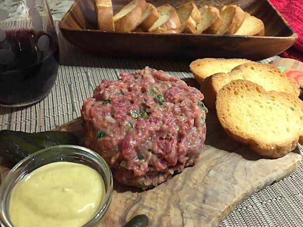 A Steak Tartare On A Wood Board With A Small Bowl Of Mustard Along With Crostini On A Beige Table Mat With A Glass Of Red Wine And A Wood Serving Dish With More Crostini.