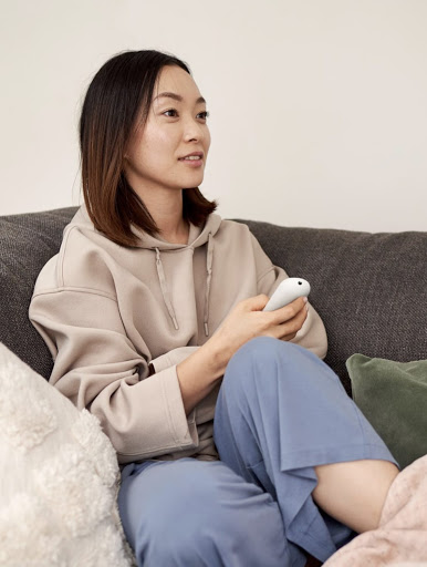 A woman sits on the couch, holding the Chromecast with Google TV remote