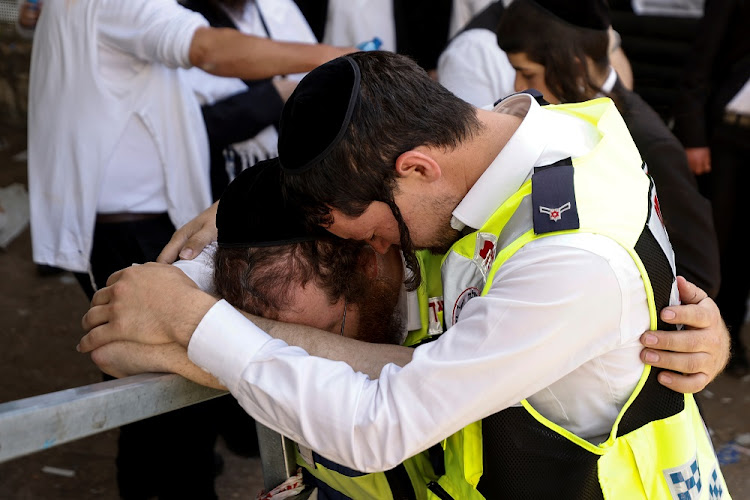 Emergency workers react upon revisiting the site where dozens were crushed to death in a stampede at a religious festival, as the country observes a day of mourning, at Mount Meron, Israel May 2, 2021.