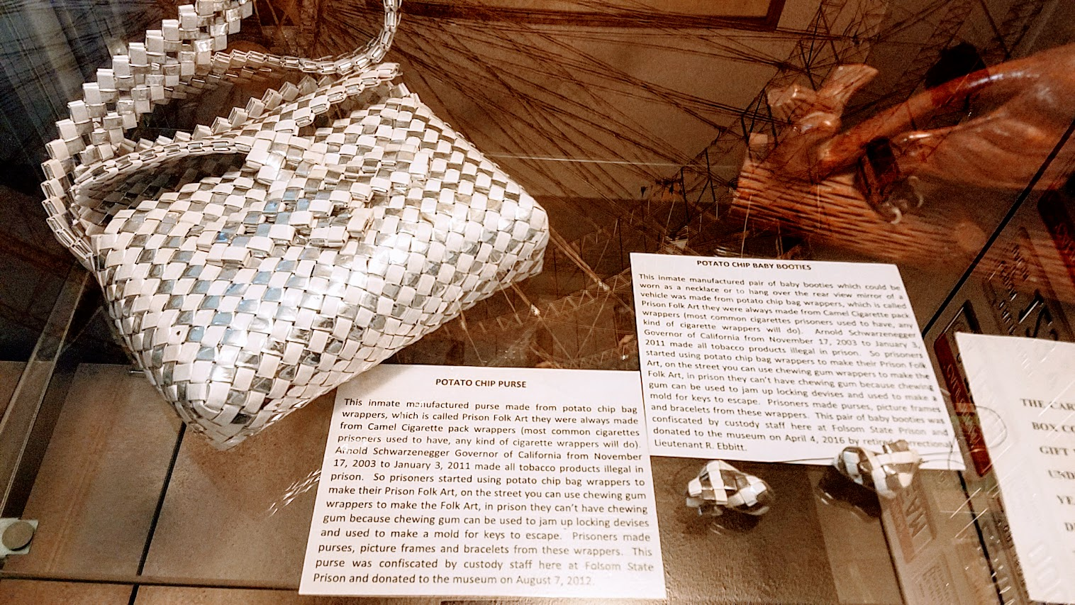 Creativity blooms with limited supplies but lots of time by the various prisoners at Folsom Prison - on display when visiting Folsom Prison Museum. This is a potato chip purse and potato chip baby boots, Prison Folk Art used to be made with cigarette pack wrappers but when tobacco products became illegal in prison, and since gum wrappers are also illegal since they can jam up locks or be used as molds, prisoners started using potato chip bags. Other objects made include picture frames and bracelets. width=