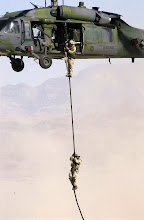 Photo: NELLIS AIR FORCE BASE, Nev. -- Airmen from the 58th Rescue Squadron here rappel from their HH-60 Pave Hawk helicopter during a simulated rescue a downed pilot.  The simulation was part of a quarterly firepower demonstration which shows off the Air Forces' full array of warfighting capabilities.  (U.S. Air Force photo by Airman 1st Class Brian P. Ferguson)