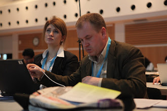 "Photo: Alyna Suslova and Stanislav Naumov - watching the panel on ""Communicating Science & Innovations"" - 2012"
