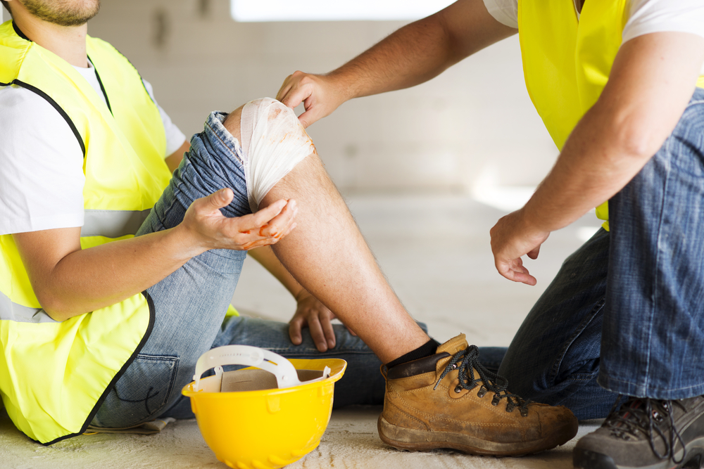 A worker helps bandage the injured knee of a fellow worker