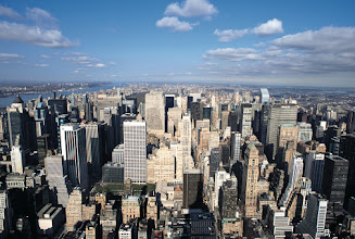 Photo: a shot of New York city from above with its skyscrapers and blue sky streaked with clouds