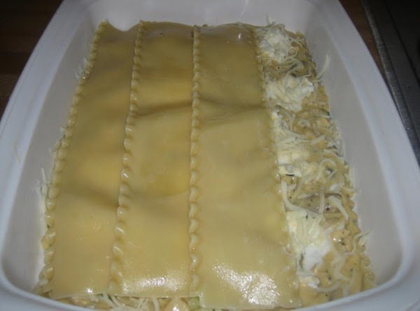 Repeat with another layer of noodles, chicken mixture, ricotta, and 1/2 a cup of...