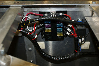 Photo: Fuse Block with wrapped, with soon-to-be-secured, cable harness.  New Ignition Kill Relay (replacing original engine disable/kill switch) is to the right of the fuse panel.  Self-adhesive tie-wrap hold downs were used temporarily during rewiring and would be replaced by proper cable clamps.  Photo by J. Loucks