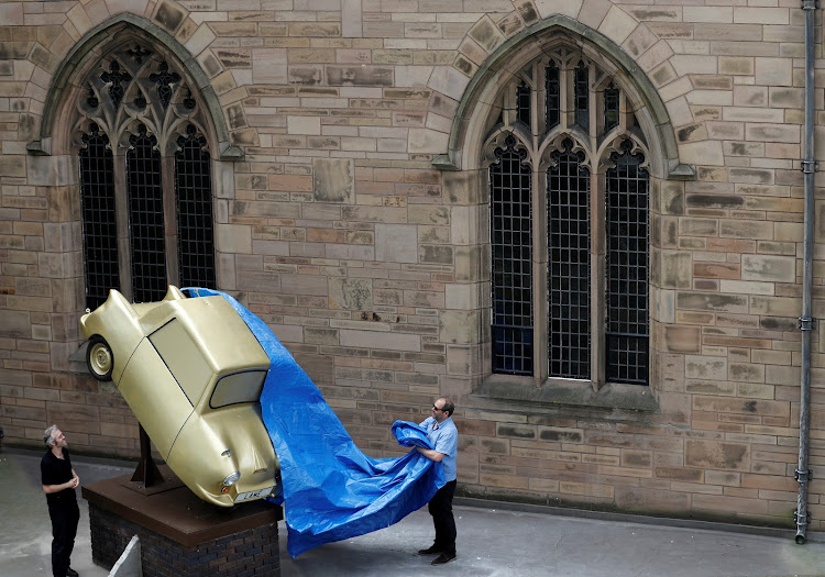 Workers unveil 'Gold Lamé', an installation by disabled artist Tony Heaton, in Liverpool on Tuesday.