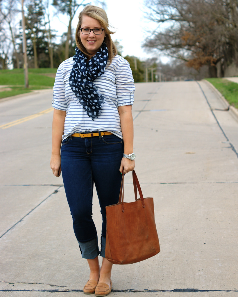 woman in jeans, t-shirt and scarf, carrying a handbag
