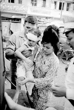 Photo: Ho Chi Minh City, Vietnam --- A rescue worker helps a mother carry her injured child to an ambulance following the bombing of an American billet by Vietcong terrorists during the Vietnam War. Ten people, including two Americans, were killed and about 175 persons were wounded as a result of the blast. --- Image by © Bettmann/CORBIS