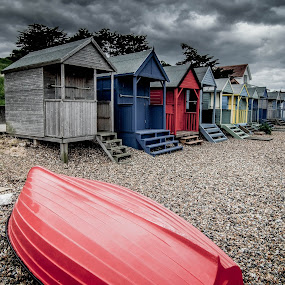 Kentish Beach Huts by Phil Clarkstone - Buildings & Architecture Other Exteriors ( upturned, shack, pebbles, seaside, storm clouds, beach, storm, boat, shacks, clinker, wooden, red, huts, blue, summer, shingle, english )