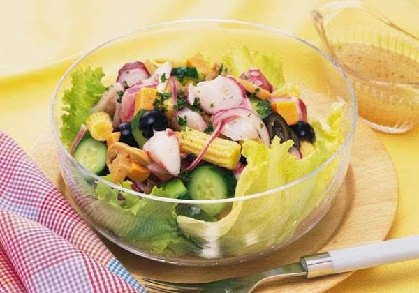 glass bowl of salad including relish, corn, cucumber and onions