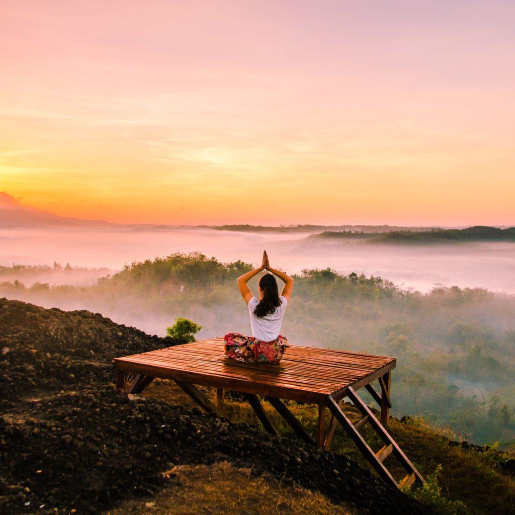 женщина занимается медитацией в лесу