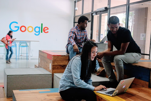 Google employees sitting in workspace with Google logo in the background.