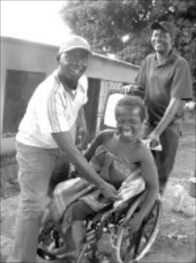 JOYOUS MOBILITY: Matsie Malatji, in the wheelchair, with community development worker Strawberry Makgoba, and councillor Masilu Maloko from the Greater Tzaneen municipality. Pic. Alex Matlala. 16/10/07. © Sowetan.