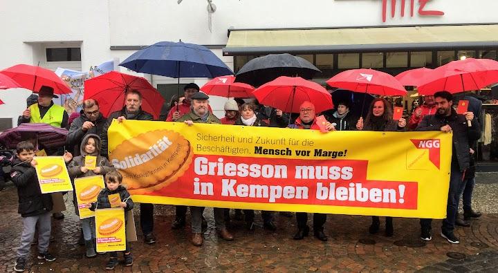 Gruppenbild Demonstrant*innen mit Regenschirmen und Plakaten. Transparent: «Sicherheit und Zukunft für die Beschäftigten. Mensch vor Marge! Griesson muss in Kempen bleiben! Solidarität mit den Kolleg*innen in Kempen!».