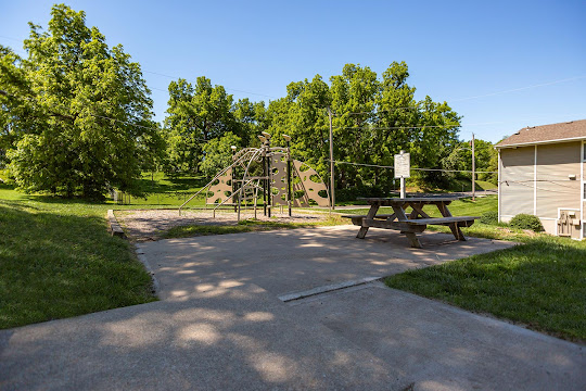 Playground area featuring monkey bars, climbing structures, outdoor picnic table
