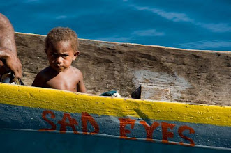 Photo: Young boy in a carved out boat