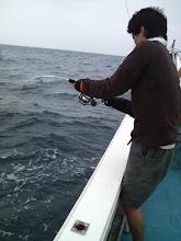 """Photo: ジギング初挑戦の""""ヨシムラさん""""に待望のヒット! ドラグが・・・! ハンドルが巻けない・・・!  船頭の18番「巻け―!とにかく、巻け―!」が響きわたる!ちょっとだけ応援して、そして・・・。"""