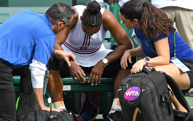 Serena Williams of the United States receives medical attention for a viral infection during her match against Garbine Muguruza of Spain in the second round of the BNP Paribas Masters on March 10, 2019 at the Indian Wells Tennis Garden in Indian Wells, California.