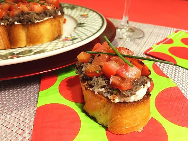 A Slice Of Bread With Cheese, Mushroom Paste And Tomato Pieces Garnished With Chives.