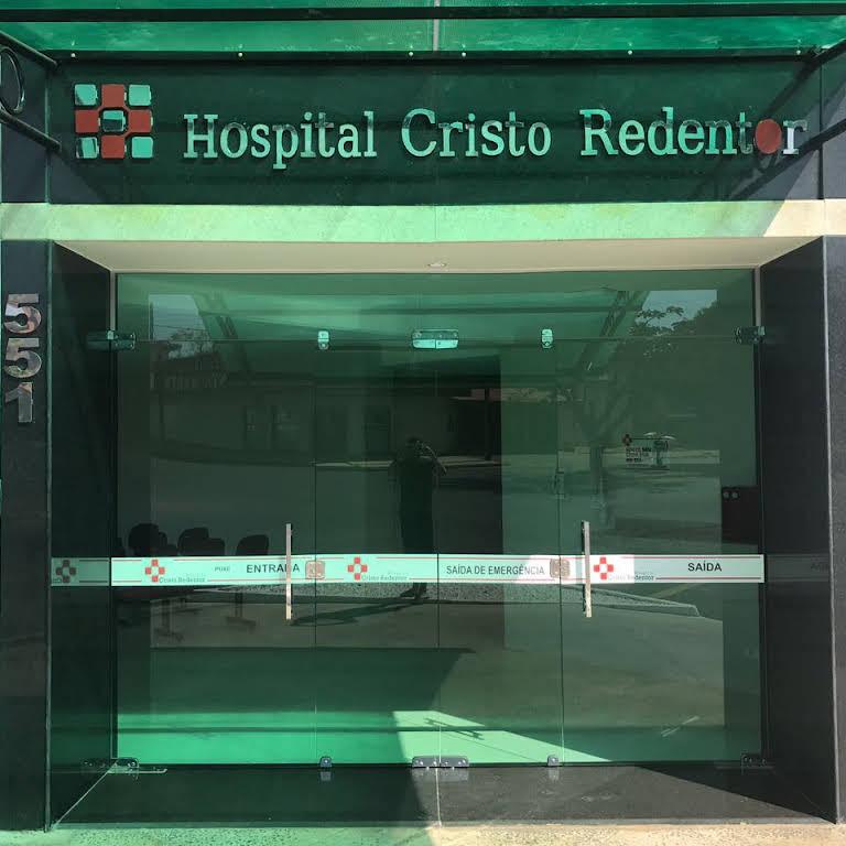 FAchada do prédio dohospital Cristo Redentor. Entrada com vidros verdes e nome do hospital em destaque