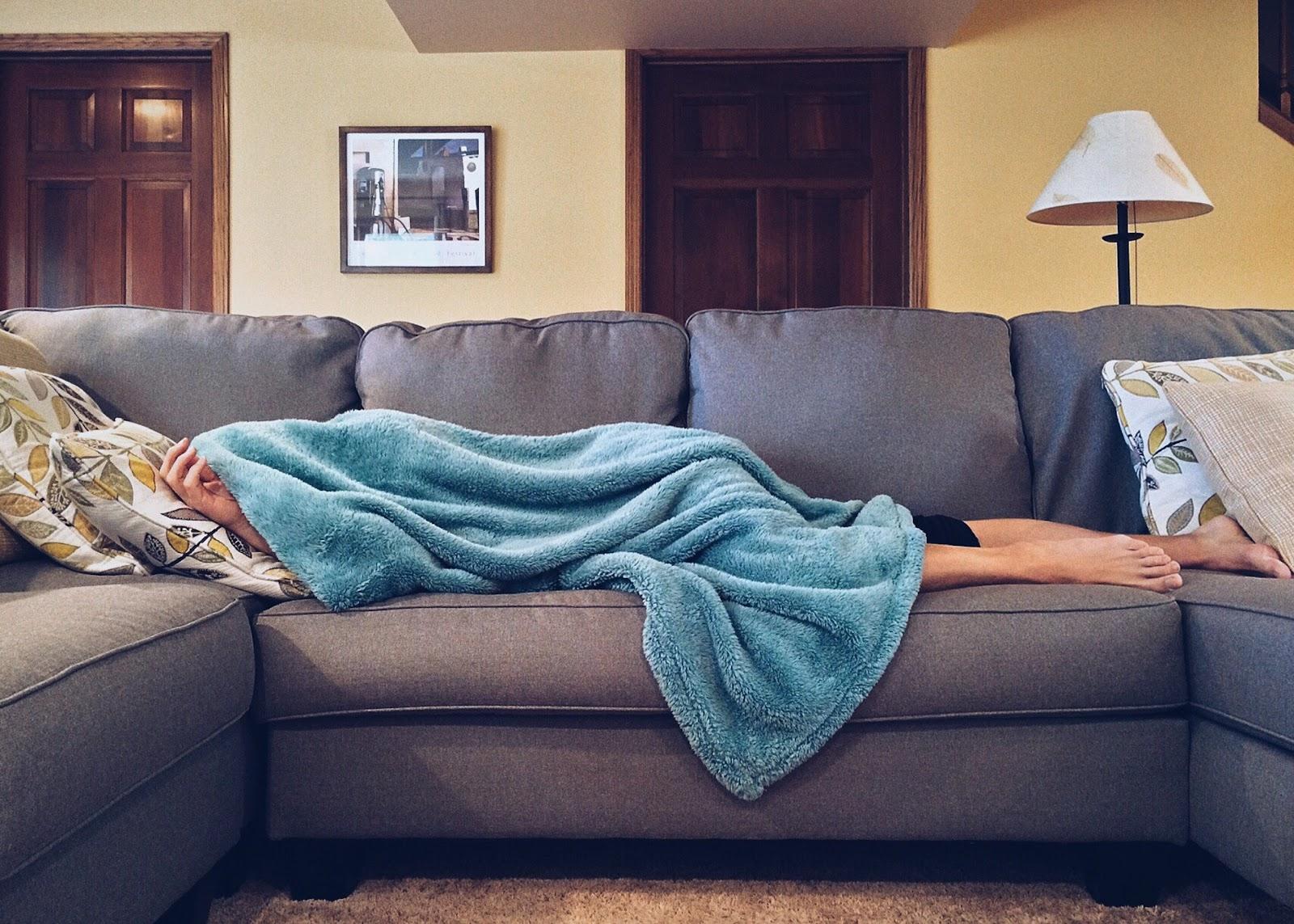 אישה שוכבת על הספה מכוסה
