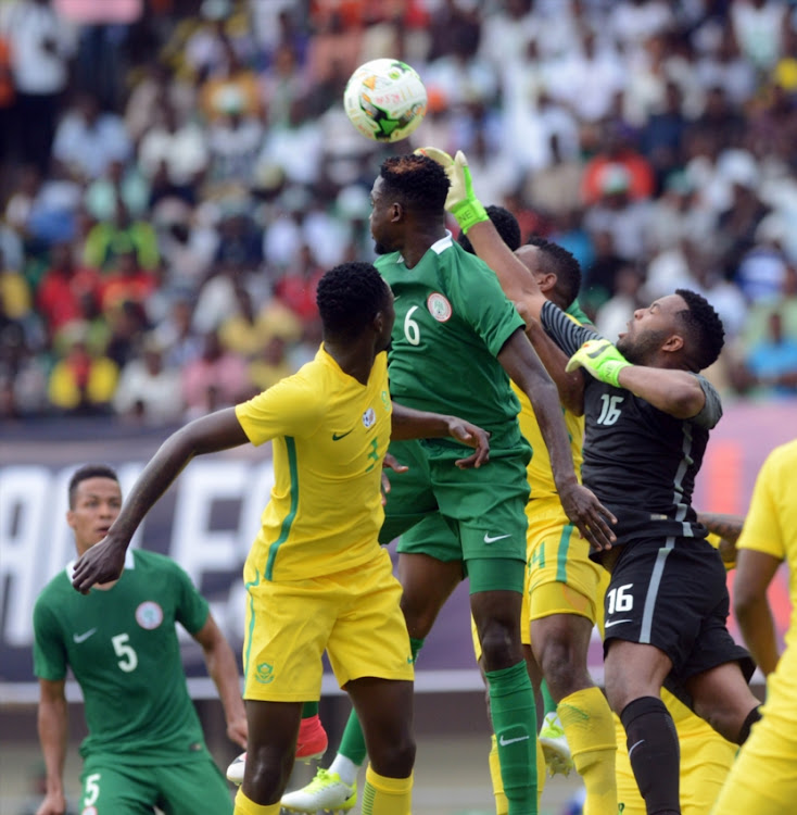 Wilfred Ndid of Nigeria contest the ball Itumeleng Khune of South Africa during the 2019 Africa Cup of Nations Qualifying match between Nigeria and South Africa at Godswill Akpabio International Stadium on June 10, 2017 in Uyo State, Nigeria.