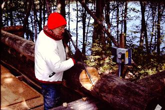 Photo: Lorraine notching a log. 1992
