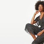 Woman sitting down wearing a black glitter jumpsuit