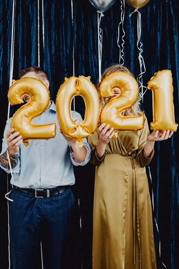 foto de um casal segurando balões em formato de número com a sequência 2021
