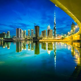 Dubai Reflection by RJ Ramoneda - Buildings & Architecture Bridges & Suspended Structures ( water, pwcarcreflections, clouds, digital blending, reflection, dubai, business bay, blue hour, cityscape, bridge, architecture, burj khalifa )