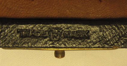 Photo: Image of the 'TRADE R MARK' stamp on a TRM set similar to mine (but with a leather playing field) - original photo, from which the above was cropped, kindly provided by Jon Crumiller.  This clearly shows the shape of the 'border' to the 'R': but does it stand for 'Rue' in de la Rue? It could stand for 'Registered', but I can't recall seeing it used in that context before. [From an advert provided by Mick Deasey to Guy Lyons, we now have evidence that these sets were made in the USA - the advert includes this logo at the top]    This stamp features - more or less clearly - on all the TRM sets (by, of course, definition!) that I have seen or heard of.