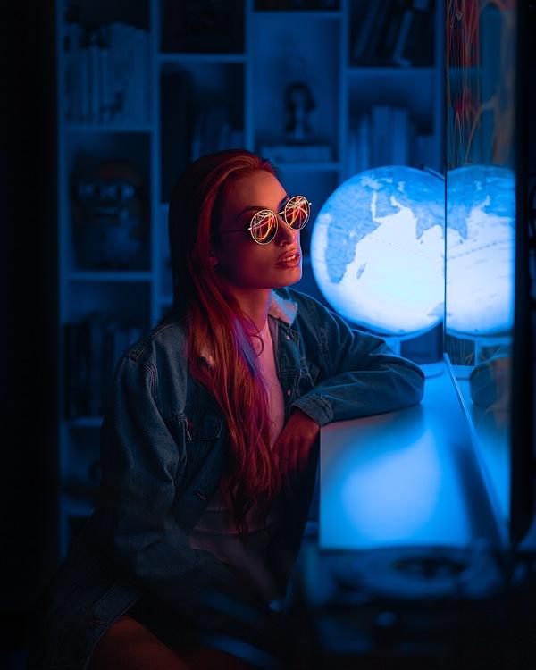 Foto de uma mulher dentro de casa com um globo azul ao lado
