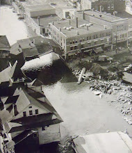 Photo: All that remained of the businesses along the Main Street bridge in Torrington were the rooftops.