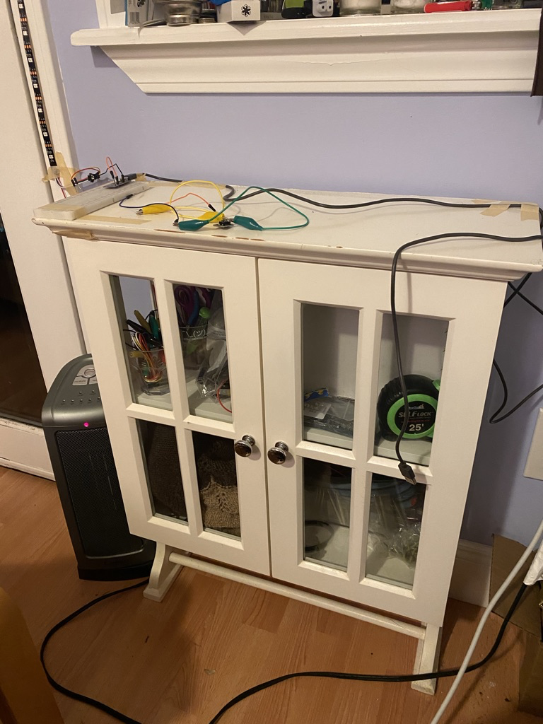 A small cabinet with electronics set up on top