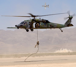 Photo: NELLIS AIR FORCE BASE, Nev. -- An HH-60G Pave Hawk retrievs a pararescueman as an A-10 Thunderbolt II provides cover fire during a firepower demonstration on the bombing range here May 12. The pararescueman is a member of the 58th Rescue Squadron. (U.S. Air Force photo by Senior Airman Kenny Kennemer)