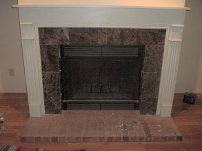 Photo: installing dark marble on fire place will go over brick on floor.