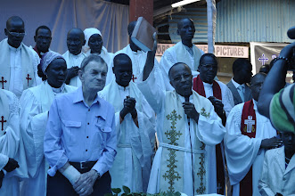 Photo: Standing with the pastors of the East Gambella Bethel Synod, EECMY Mission & Theology director, Rev. Yonas Yigezu presents the Bible to the people. (The blue hue is from the blue tarp blocking out the hot sun.)