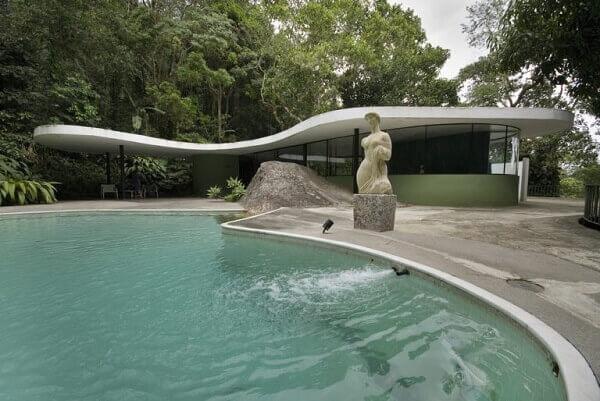 Fotografia da casa das Canoas, onde Niemeyer morou. A cobertura curvilínea, segue os traços da piscina. Ambos são complementados por uma bela escultura feminina.