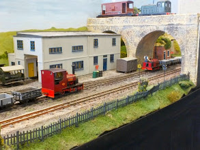 Photo: 016 A busy scene outside the workshop building. 2 small Hunslets are shunting, whilst the PW Dept Wickham trolley is waiting to enter the workshop and a diesel loco hauls a brakevan across the standard gauge bridge .
