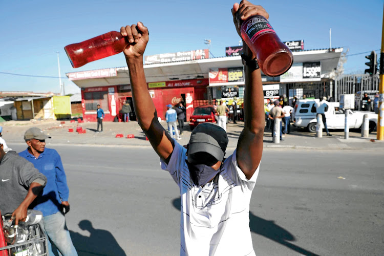 A man celebrates with his liquor after standing in a queue to buy the bottles in Nyanga, Cape Town. Picture: Esa Alexander