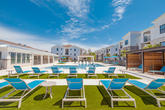 Resort-style swimming pool with lounge space and chairs
