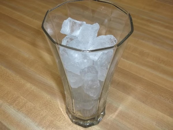 Fill a tall glass with ice cubes.